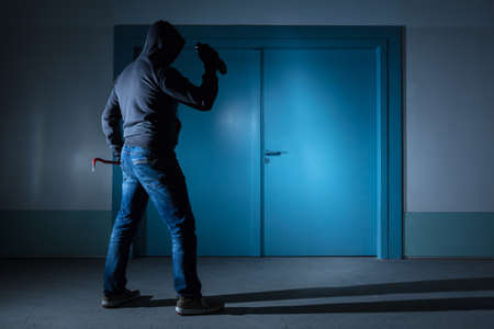 thievery: Rear View Of A Thief With Flashlight And Crowbar Standing Outside The Door