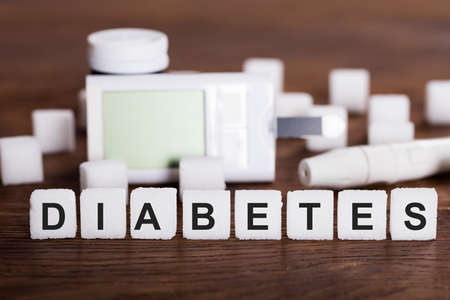 sweeten: Diabetes Kit And Sugar Cubes With Text Diabetes On Wooden Desk Stock Photo