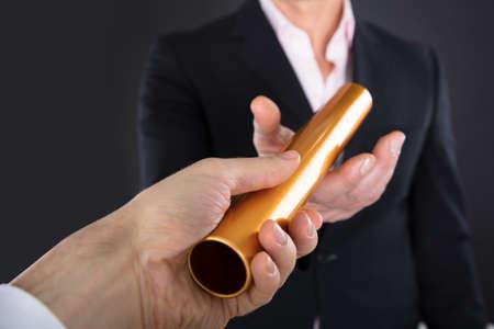Close-up van een zakenman Passen Golden estafettestokje naar collega Stockfoto