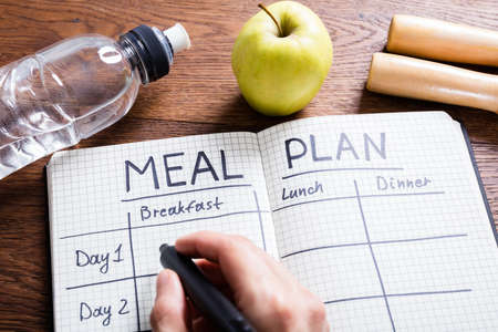 diet plan: High Angle View Of A Person Hand Filling Meal Plan In Notebook At Wooden Desk Stock Photo