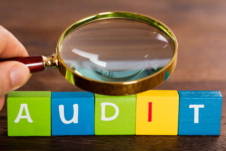 Person Hand With Magnifying Glass Over The Word Audit On Cubes