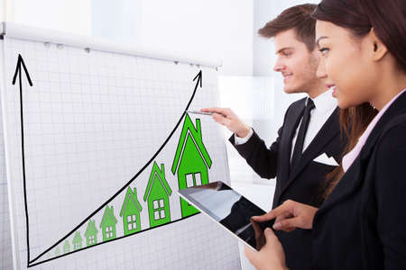 Two Successful Businesspeople Working On House Raise Concept On Flipchart Using Digital Tablet Stock Photo - 71451425