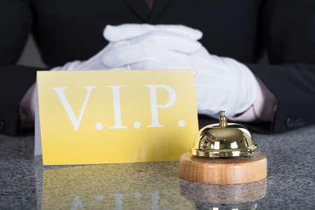 Close-up Of A Waiter Hand Near Service Bell And VIP Card On Desk