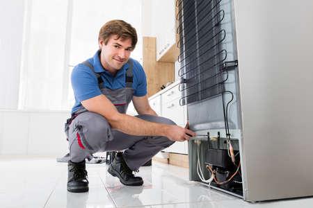 El mecánico masculino de los jóvenes que trabaja en la nevera con destornillador en el hogar