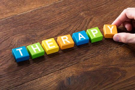 Gros plan d'un concept de thérapie sur un bloc coloré au bureau en bois Banque d'images - 71451456
