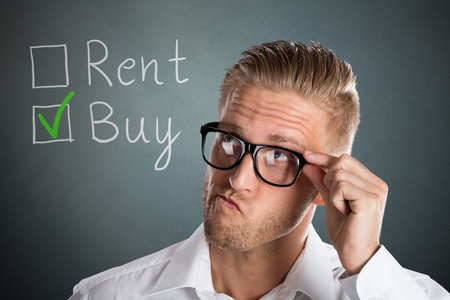 buying questions: Young Handsome Business Man Choosing Rent Or Buy Option For Real Estate Property Stock Photo