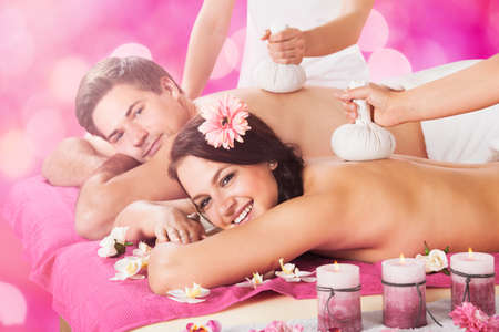 Young Couple Getting Massage With Herbal Compress Balls On Back At Beauty Spa In Spa