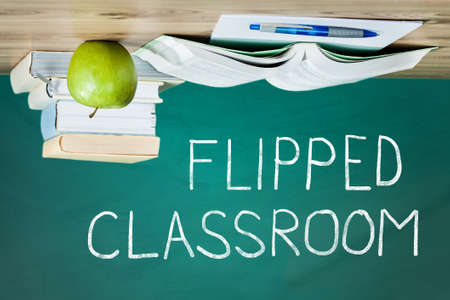 flipped: Flipped Classroom Concept On Blackboard With Stacked Book And Apple On Wooden Table Stock Photo