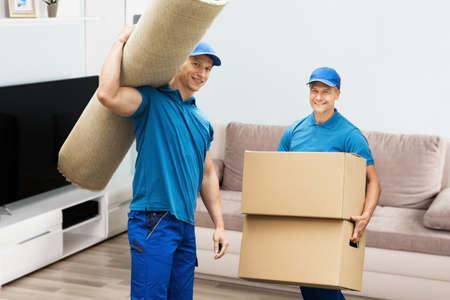 カーペットと家の中の段ボール箱を運ぶ 2 つの男性労働者の肖像 写真素材