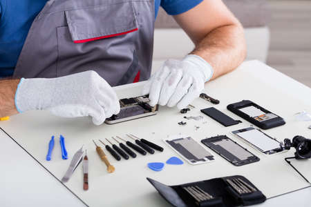 Close-up Of Person's Hand Wearing Glove Repairing Cellphone Using Screwdriver Archivio Fotografico