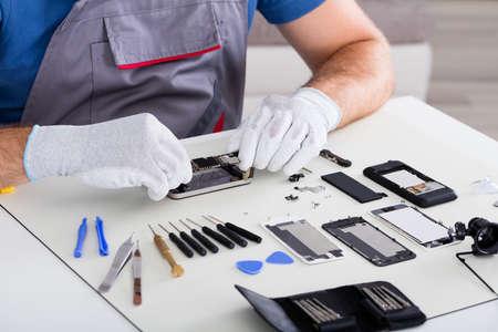 Close-up der Person Hand tragen Handschuh Reparatur Handy mit Schraubendreher