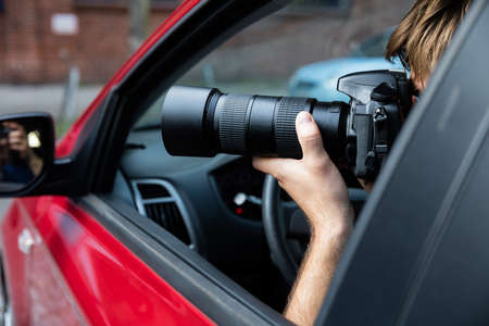 Private Detective Sitting Inside Car Photographing With SLR Camera Stock Photo - 71451474