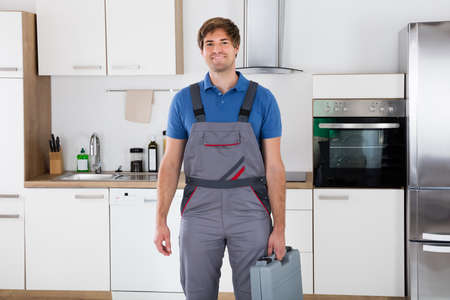 happy worker: Portrait Of A Happy Young Worker Holding Toolbox Standing In Kitchen