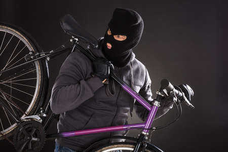 robbed: Person Wearing Balaclava Stealing A Bicycle On Black Background Stock Photo