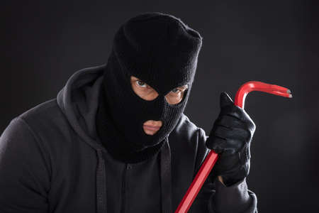 crowbar: Portrait Of A Burglar Wearing Balaclava Holding Crowbar On Black Background