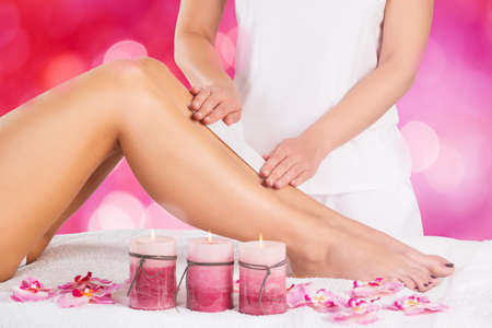 depilate: Close-up Of A Beautician Waxing Leg Of Woman With Wax Strip At A Beauty Spa Stock Photo