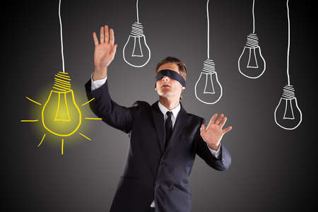 lost in thought: Blindfolded Businessman Searching For Bright Idea Concept On Gray Background