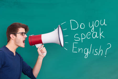 Young Man Doing Announcement Of English Speaking Using Megaphone On Blackboard photo