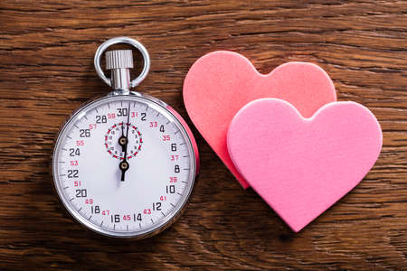 Speed Dating Concept. Two Heart Shapes And A Stop Watch On Wooden Desk