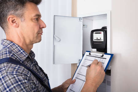clipboard: Close-up Of A Male Technician Writing Reading Of Meter On Clipboard Stock Photo