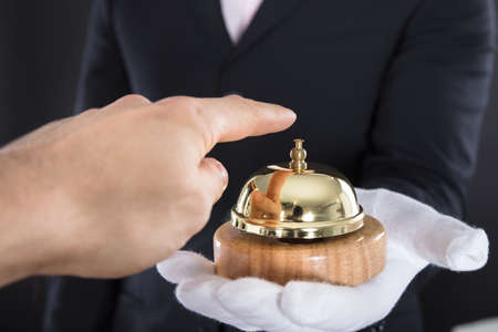 Close-up Of A Persons Hand Ringing Service Bell Hold By Waiter Stock Photo