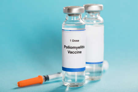 antigenic: Poliomyelitis Vaccine Bottles With Syringe Over Turquoise Background Stock Photo