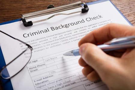 Gros plan de remplissage des antécédents criminels Formulaire de vérification de l'application de la personne à la main Banque d'images