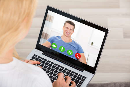 Close-up Of Young Woman Videoconferencing With Man On Laptop. Online Dating Concept