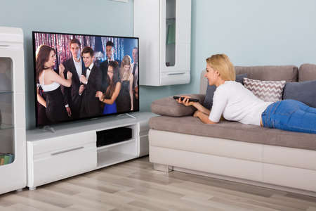 changing channel: Young Woman Lying On Sofa Watching Movie On Television At Home Stock Photo