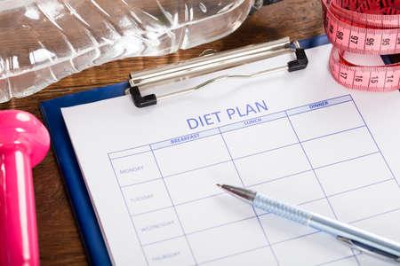 portapapeles: Plan de dieta con una pesa, botella de agua y cinta de medición en el escritorio de madera