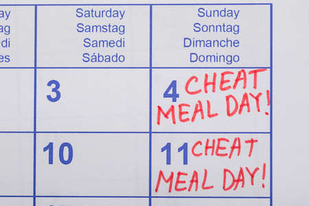 cheat: Close-up Of Cheat Meal Day Text Written On Calendar Date Stock Photo