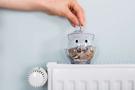 Close-up Of Person Hand Inserting Coin In Transparent Piggybank Kept On Radiator