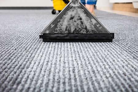Close-up de um tapete de limpeza com aspirador de pó