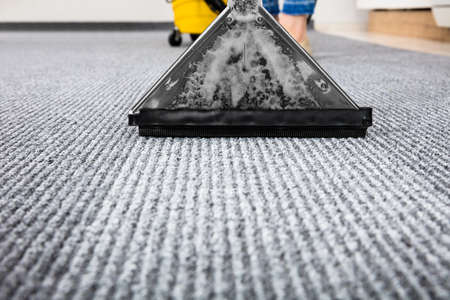 chores: Close-up Of A Cleaning Carpet With Vacuum Cleaner