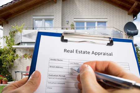 Close-up Of Person Hand Filling Real Estate Appraisal Document In Front Of House