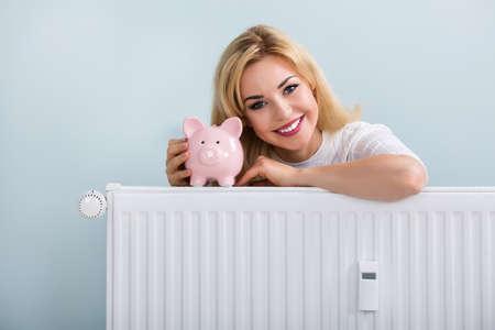 piggybank: Young Happy Woman With Piggybank On Radiator At Home