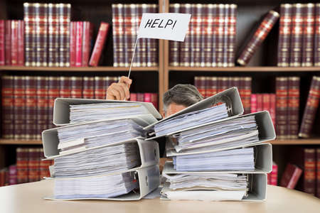 bookkeeping: Close-up Of A Accountant Holding Help Flag Between The Stacked Folders On Desk In Courtroom