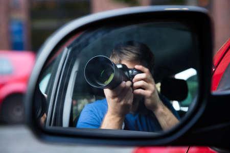 Detective privado que se sienta en la fotografía del coche reflejada en espejo de ala Foto de archivo - 72006381