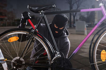 Thief Trying To Break The Bicycle Lock Parked Near The Roadside