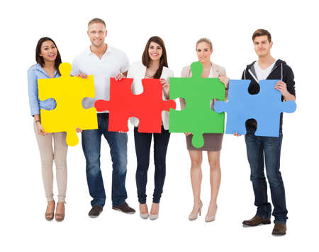 Group Of A People Assembling Jigsaw Puzzle On White Background Stock Photo