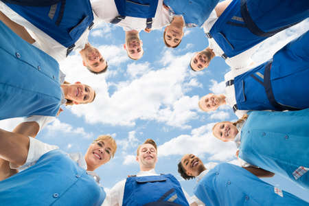 Portrait Of A Confident Janitors Standing In Huddle Against Sky photo