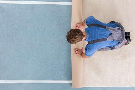 Erhöhte Ansicht der Handwerker in dem Gesamten Abrollen Teppich Auf dem Boden