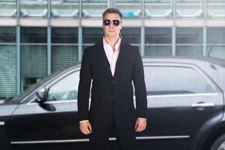 車の前に立っている深刻な男性警備員の肖像画