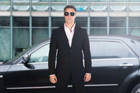 자동차 앞에 서있는 심각한 남성 보안 가드의 초상화 스톡 콘텐츠