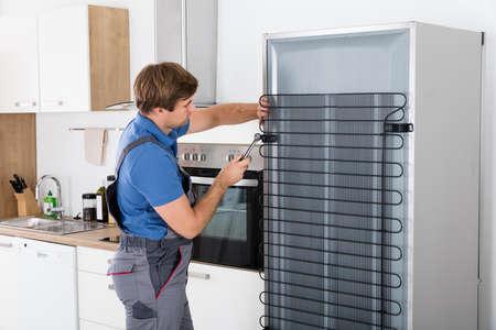 Serviceman In Overall Arbeiten Auf Kühlschrank Mit Schraubendreher In Küche