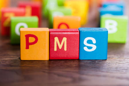 premenstrual syndrome: PMS Word Made With Colorful Blocks On Table Stock Photo