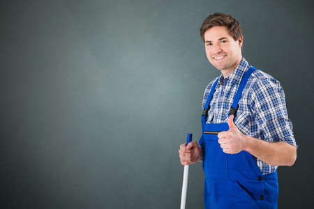 sweeper: Portrait Of A Smiling Male Janitor On Gray Backgrounds