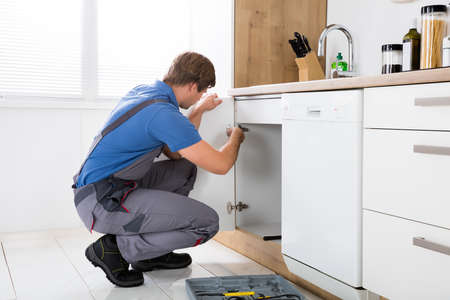 Repairman In Overalls Repairing Cabinet Hinge In Kitchen Stock Photo - 72006430