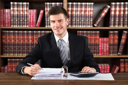 law suit: Portrait Of A Young Male Accountant Calculating Financial Document Stock Photo