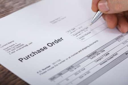 Close-up de uma pessoa Mão Enchendo Um Purchase Order Form na mesa de madeira